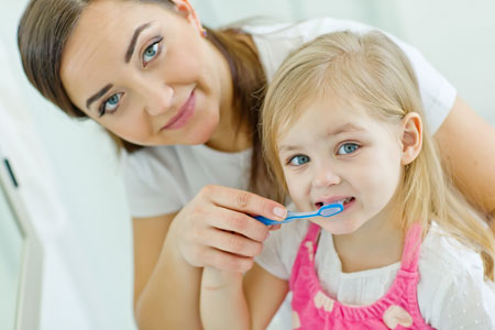 Mom and Daughter brushing their teeth - Pediatric Dentist in Macon, GA